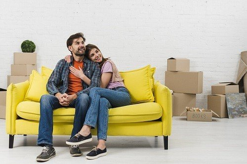 couple is waiting for house moving on a sofa